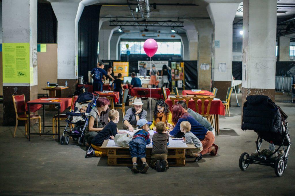 Des personnes en train de dessiner autour d'une table, au sein de l'Union Sociale. Crédits photo Vincent Muller.